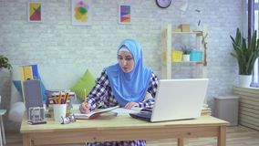 Mulher muçulmana nova bonita no hijab, estudando em apartamentos modernos video estoque