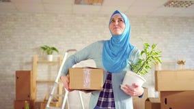 Mulher muçulmana nova do retrato em um hijab com uma flor e uma caixa em suas mãos