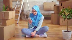 A mulher muçulmana nova do retrato em um hijab usa o smartphone que senta-se no assoalho ao lado das caixas em um apartamento mod