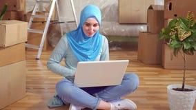 A mulher muçulmana nova do retrato em um hijab usa um portátil que senta-se no assoalho ao lado das caixas