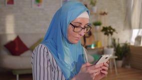 A mulher muçulmana nova do retrato no hijab com uma cicatriz de uma queimadura em sua cara usa um smartphone vídeos de arquivo