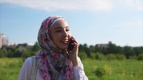 Mulher muçulmana nova e moderna no hijab que fala no telefone celular no parque video estoque