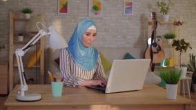 Mulher muçulmana nova em um hijab com uma cicatriz de uma queimadura em seus trabalhos da cara em um portátil filme