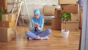 A mulher muçulmana nova em um hijab usa o smartphone que senta-se no assoalho ao lado das caixas em um apartamento moderno