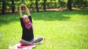 A mulher muçulmana nova em um lenço estica sua espinha no parque em um dia de verão video estoque