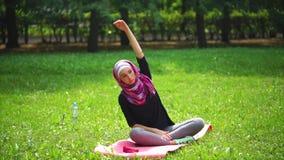 A mulher muçulmana nova em um lenço estica sua espinha no parque em um dia de verão vídeos de arquivo