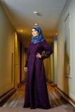 Mulher muçulmana nova na roupa islâmica na moda, estando no corredor do hotel Foto de Stock