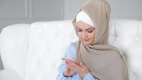 A mulher muçulmana nova no hijab bege e no desgaste tradicional está conversando no telefone celular
