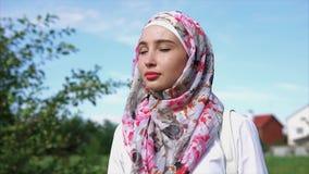 Mulher muçulmana nova no hijab brilhante, retrato exterior filme
