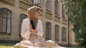 Mulher muçulmana nova no hijab que senta-se na grama e que tem o bate-papo video através da tabuleta, mostrando o lugar a alguém vídeos de arquivo