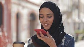 Mulher muçulmana nova que envia a mensagem audio da voz no telefone celular na fala exterior ao assistente móvel Utiliza??o da me video estoque