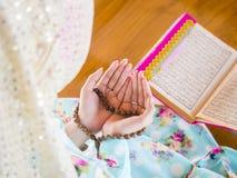 Mulher muçulmana nova que reza para Allah imagem de stock
