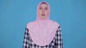 A mulher muçulmana nova que tem o problema que respira o nariz ralo, usa o pulverizador de nariz filme