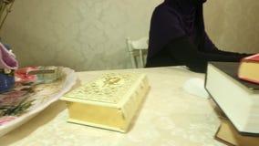 Mulher muçulmana nova que trabalha na mesa, nos originais e no computador de escritório filme