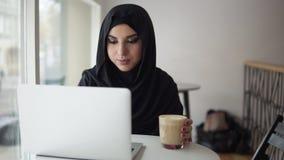 Mulher muçulmana nova que trabalha no portátil moderno no café e no cappuccino bebendo Mulher atrativa no hijab que procura por video estoque