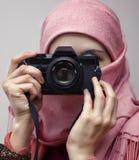 Mulher muçulmana que toma uma fotografia com uma câmera do slr Foto de Stock