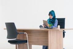 Mulher muçulmana que usa a tabuleta digital na tabela do escritório imagens de stock