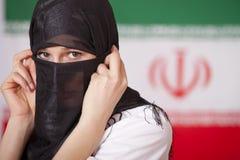 Mulher muçulmana sobre a bandeira de Irã Fotografia de Stock Royalty Free