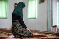 Mulher mu?ulmana nova que reza na mesquita fotografia de stock