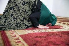Mulher mu?ulmana nova que reza na mesquita imagens de stock royalty free