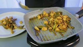 Mulher muda frango frito com feijão verde e cogumelos de uma frigideira para um prato branco filme