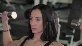 Mulher muito bonita da aptidão que exercita com pesos no gym vídeos de arquivo