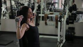 Mulher muito bonita da aptidão que exercita com pesos no gym video estoque