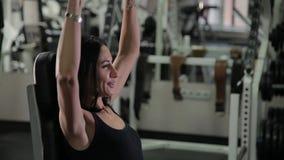 Mulher muito bonita da aptidão que exercita com pesos no gym filme