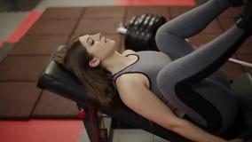 A mulher muito bonita da aptidão treina seus pés no simulador no gym filme