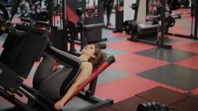 A mulher muito bonita da aptidão treina seus pés no simulador no gym video estoque