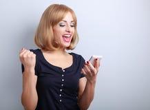 Mulher muito entusiasmado feliz que olha seu telefone celular e que lê s Imagens de Stock