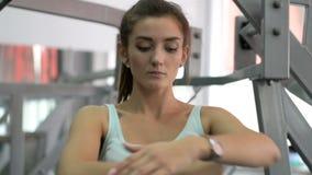 Mulher muito flexível que estica em uma esteira do exercício durante um exercício filme