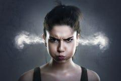 Mulher muito irritada com o fumo que sai de suas orelhas foto de stock