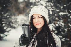 A mulher muito positiva bebe o café no parque do inverno Retrato do inverno da mulher nova fotografia de stock