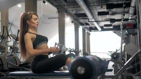 A mulher muscular bonita do ajuste que exercita a construção muscles, esporte interno do treinamento do gym do exercício do atlet vídeos de arquivo