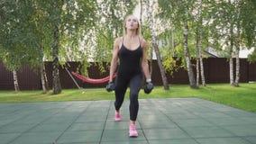 A mulher muscular da aptidão que faz o passeio investe contra com pesos no parque vídeos de arquivo