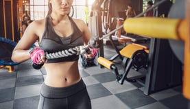 Mulher muscular da aptid?o que faz exerc?cios Conceito do estilo de vida saud?vel Halterofilista apto transversal no gym imagem de stock