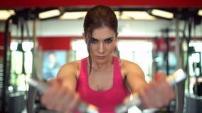 Mulher muscular do atleta em uma parte superior cor-de-rosa que dá certo em levantar peso do gym menina da aptidão que exercita n filme