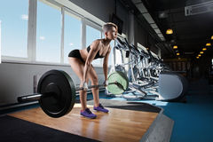 Mulher muscular em um gym que faz exercícios pesados Fotografia de Stock Royalty Free