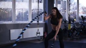 Mulher muscular forte que dá certo com cordas da batalha Metragem de uma mulher atrativa no sportswear preto no gym lento video estoque