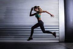 Mulher muscular que corre na sala de exercício fotografia de stock