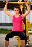 A mulher muscular que senta-se em pesos faz à máquina o exercício dos braços Imagem de Stock