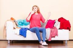 A mulher não conhece o que vestir o assento no sofá Foto de Stock Royalty Free