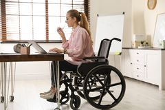 Mulher na água potável da cadeira de rodas imagens de stock royalty free