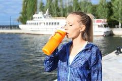 Mulher na agitação bebendo da proteína do sportswear imagem de stock royalty free