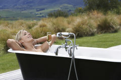 Mulher na banheira com Champagne On Countryside Porch imagem de stock