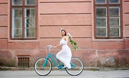 A mulher na bicicleta está montando ao longo da cidade velha com peônias imagens de stock
