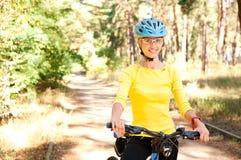 Mulher na bicicleta no ensolarado imagem de stock royalty free