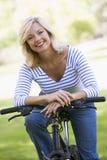 Mulher na bicicleta que sorri ao ar livre Fotografia de Stock Royalty Free