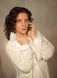 Mulher na blusa branca que fala no telefone Fotografia de Stock Royalty Free